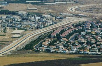 Aerial photo of West Bank showing Jewish settlements to the right of the separation wall and Palestinian homes to the left.