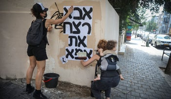 Women plaster a poster in Tel Aviv which reads 'Dad killed Mom', August 2020
