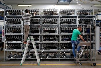 Employees work on bitcoin mining computers at Bitminer Factory in Florence, Italy, April 6, 2018. Picture taken April 6, 2018.