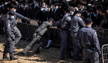 Israeli police try to control a crowd of mourners during the funeral of Rabbi Mordechai Leifer, in the port city of Ashdod, Israel, October 5, 2020.