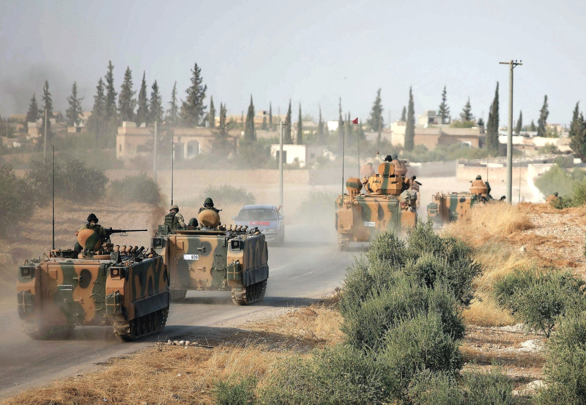 Turkish troops driving their armoured personnel carriers through the village of Qirata on the outskirts of the northern city of Manbij near the Turkish border, October 14, 2019.