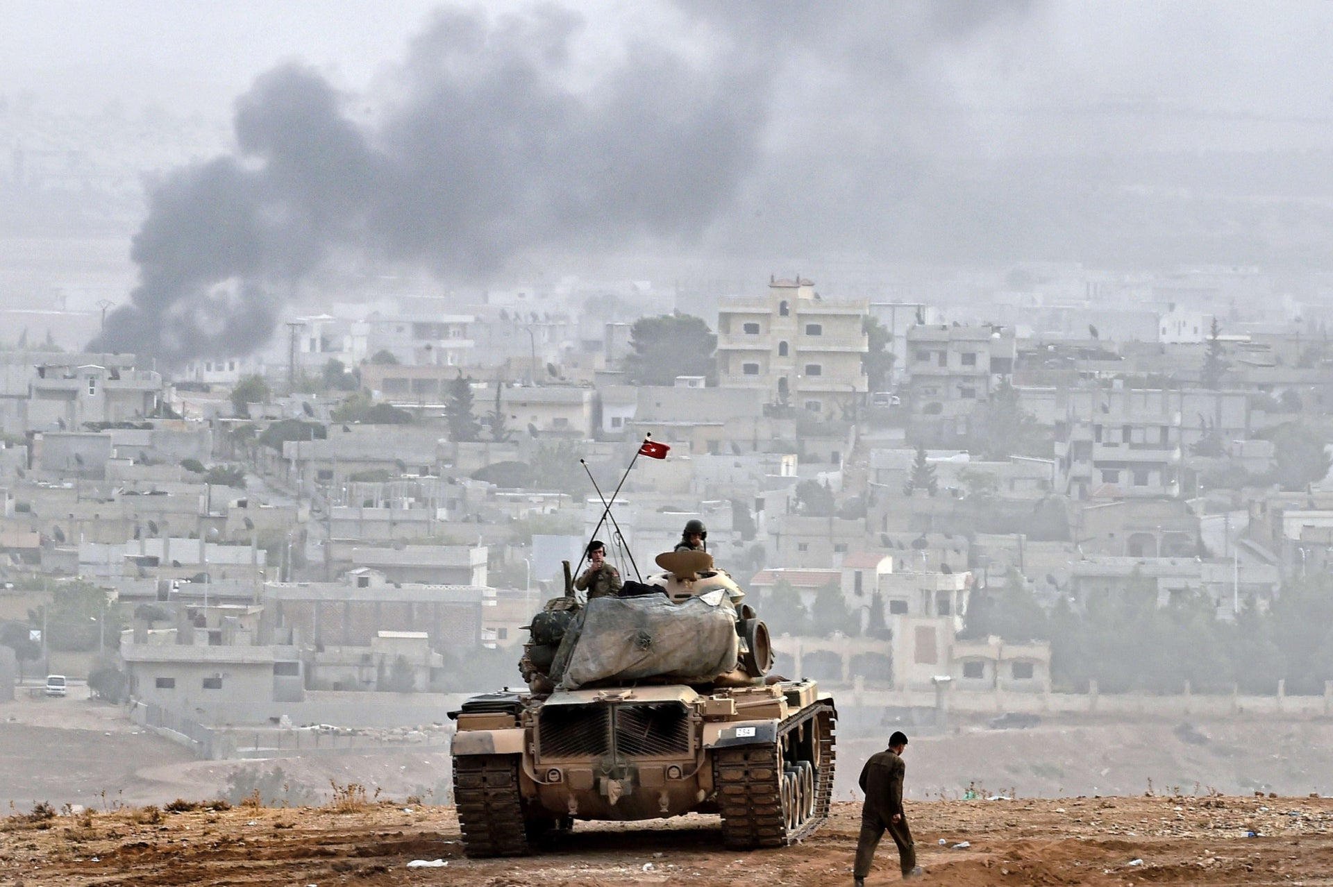 Turkish soldiers on a tank sit opposite the Syrian town of Kobane, at the Turkish-Syrian border in 2014.
