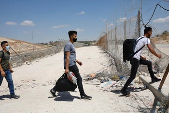 Palestinian workers cross through a hole in the separation fence into Israel, September 8, 2020.