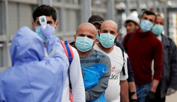 A healthcare worker checks the body temperature of Palestinian workers returning from Israel, April 7, 2020.