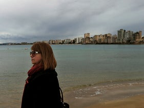 A woman stands at the beach with Famagusta or Varosha beach in the abandoned city, seen in the background, January 6, 2019.