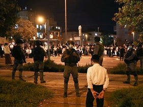 An ultra-Orthodox boy in front of police officers as they attempted to enforce coronavirus restrictions over the Sukkot holiday, Jerusalem.