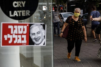A pedestrian walks by a store bearing a sticker with a picture of Netanyahu stating, 'closed because of me,' September 2020.