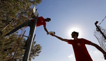 Workers install a video surveillance system in the village of Kisan in the Israeli-occupied West Bank October 6, 2020.