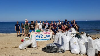The protectors of Haifa's Bat Galim Beach and some of the litter they collected.