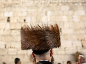 A Haredi man wearing a fur hat known as a shtreimel, in front of the Western Wall, in Jerusalem.