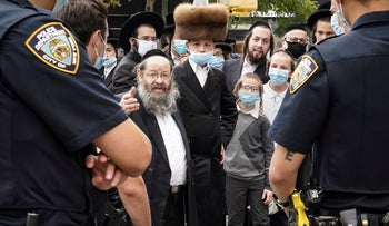 Members of the Jewish Orthodox community speak with NYPD officers on a street corner, in the Borough Park neighborhood of the Brooklyn borough of New York, October 7, 2020.