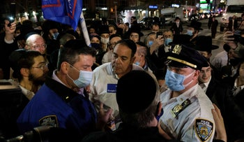 NYPD officers speak with Ultra-Orthodox Jews as they gather in the Borough Park neighborhood of Brooklyn amid the coronavirus disease outbreak in New York, October 7, 2020.
