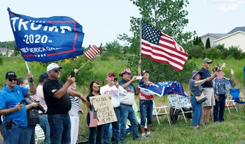 Supporters watch the motorcade of President Donald Trump drive past before an event at the Whirlpool Corporation in Clyde, Ohio. Aug. 6, 2020