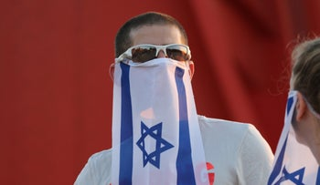 Israelis wear flags as facemasks during a demonstration against Benjamin Netanyahu's government, Jerusalem, October 6, 2020.