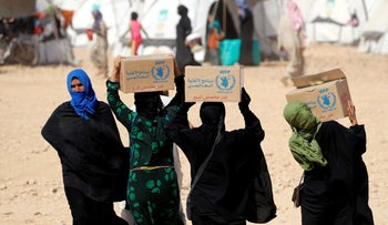 People displaced by fighting between Syrian Democratic Forces and Islamic State militants carry food aid boxes given by UN's World Food Program at a refugee camp in Ain Issa, Syria, October 10, 2017