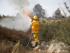 Firefighter trying to put out a fire in Kfar Oranim, October 9, 2020.