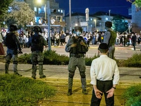 Police look on as ultra-Orthodox people gather off Highway 1 in Jerusalem, October 5, 2020.