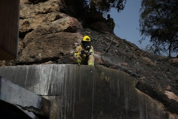 A firefighter works at a house damaged by fire in Kfar Oranim, October 9, 2020.