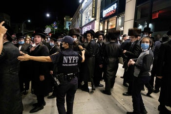 A NYPD officer speaks with Ultra-Orthodox Jews as they gather in the Borough Park neighborhood of Brooklyn amid the coronavirus disease (COVID-19) outbreak in New York, U.S. October 7, 2020.