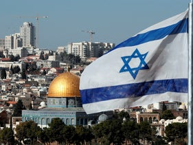 The Israeli flag flutters in front of the Dome of the Rock mosque and the city of Jerusalem, on December 1, 2017.