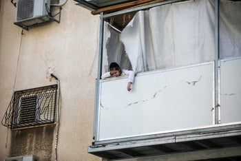 A boy looks out of his window in the ultra-Orthodox city of Bnei Brak in central Israel, one of the places hardest hit by the coronavirus, September 27, 2020.