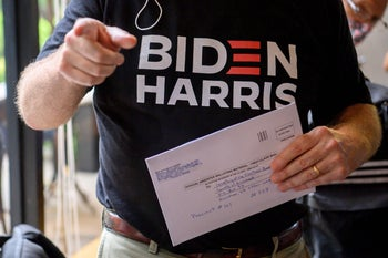 A Democrats Abroad member wearing a T-shirt reading Biden-Harris holding an envelope with his ballot for the 2020 US presidential elections the U.S. Embassy in Bangkok, September 24, 2020.