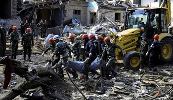 Search and rescue teams carry the body of a victim away from the blast site hit by a rocket during the fighting over the breakaway region of Nagorno-Karabakh in the city of Ganja, Azerbaijan October 11, 2020