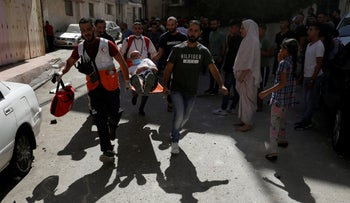 Medics and people carry a Palestinian injured during an Israeli raid in Ramallah in the West Bank, October 11, 2020.