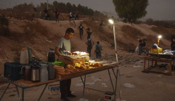 A Palestinian vendor sells food as Palestinian laborers cross illegally into Israel from the West Bank through an opening in a fence, south of the West Bank town of Hebron, Sept. 6, 2020