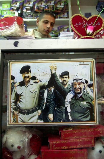 A Palestinian vendor sits behind a counter with a photo of Palestinian leader Yasser Arafatand Saddam Hussein, taken two years before Iraq's invasion of Kuwait. Jenin, Dec. 14, 2003