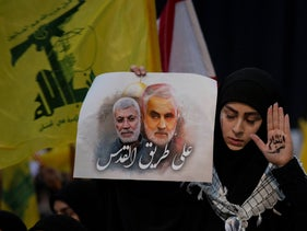 A Hezbollah supporter writes 'powerful revenge' on her hand at a rally with Hezbollah chief Hassan Nasrallah in Beirut, Lebanon, following the strike on Soleimani. Placard reads: 'On the road to Jerusalem.' Jan. 5, 2020