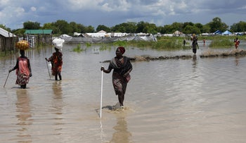 Women wade through flood waters after the River Nile broke the dykes in Pibor, Greater Pibor Administrative Area, South Sudan October 6, 2020.