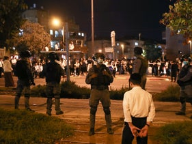Israel police stand as in front of an ultra-Orthodox crowd during the lockdown in Jerusalem, October 5, 2020.