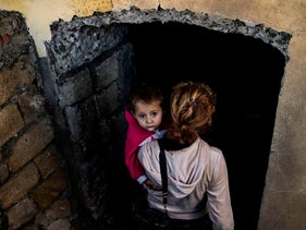 A woman carries her child into a basement to take shelter from fighting in Shusha, a town in the breakaway region of Nagorno-Karabakh. October 8, 2020