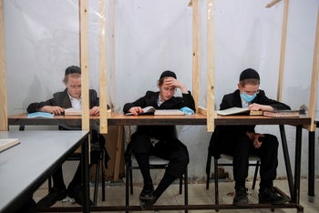 Ultra-Orthodox students study religious texts in a yeshiva using protective plastic shields set up amid the coronavirus pandemic, in Bnei Brak, Israel, August 27, 2020.
