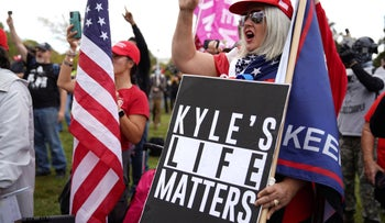 Members of the Proud Boys and other right-wing demonstrators carry signs in support of Kyle Rittenhouse during a rally in Portland, Oregon, September 26, 2020.