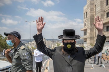 An ultra-Orthodox man wears a mask sporting a yellow star with the German word 'Jude' written across it to protest a coronavirus lockdown in Jerusalem, July 10, 2020.