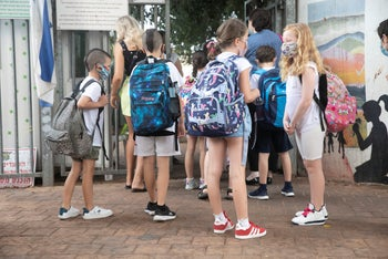Children outside a school on the first day of the year, September 1, 2020.