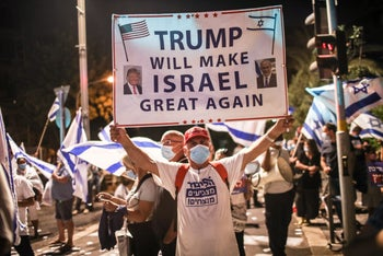 A protester holds up a pro-Trump sign at a demonstration in support of Prime Minister Benjamin Netanyahu, Jerusalem, July 23, 2020.
