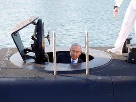 Israeli Prime Minister Benjamin Netanyahu climbs out after a visit inside the Rahav, the fifth submarine in the fleet, after it arrived in the Haifa port, January 12, 2016.