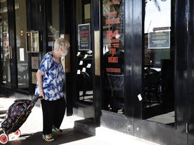A woman stands next to a closed restaurant during the coronavirus crisis, Tel Aviv