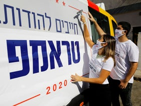 Activists from Republicans Overseas Israel paste a pro-Trump election campaign ad on a minibus in Tel Aviv, Israel October 14, 2020.