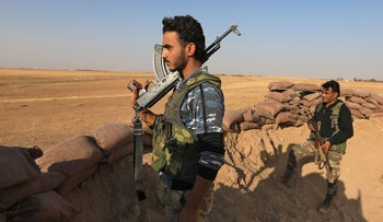 Turkey-backed Syrian fighters man a sand barricade near the rebel-controlled town of Tal Abyad in the northern Syria's Raqa province, along the frontline with Syrian Kurdish forces, October 10, 2020.