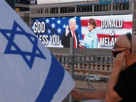 An Israeli anti-government protester lifts a national flag on an overpass facing a large billboard depicting the US President Donald Trump and his wife Melania, Tel Aviv, October 3, 2020.