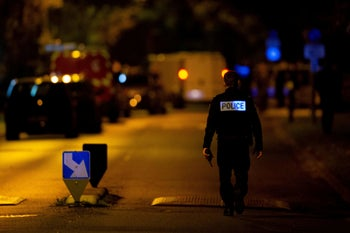 A French police officer stands guard a street in Eragny on October 16, 2020