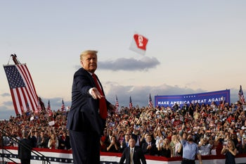 U.S. President Donald Trump throwing a face mask from the stage during a campaign rally at Orlando Sanford International Airport in Florida, October 12, 2020.