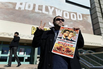 """A filmgoer holding a poster of """"The Interview"""" as the film opens in Los Angeles on December 25, 2014, defying a North Korean threat to target U.S. movie theaters."""