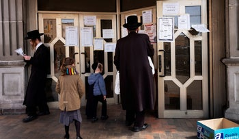 A man stops to read announcements posted on the doors of Congregation Divrei Yoel in the Williamsburg neighborhood of Brooklyn, New York, April 7, 2020.