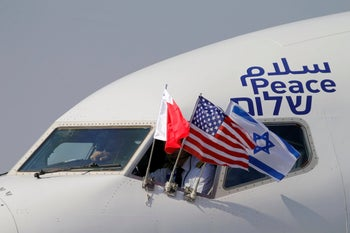 Bahraini, Israeli and U.S. flags are seen on El Al's airliner carrying Israeli and U.S. delegations as it lands in Bahrain, October 18, 2020.