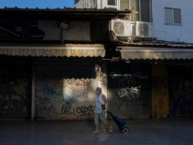 A woman wearing face mask walks past closed shops in Tel Aviv, Oct. 13, 2020.